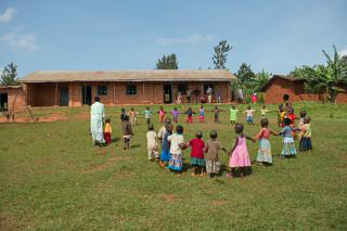 Two teachers lead a class of little children in a ring, low brick school buildings in the background.
