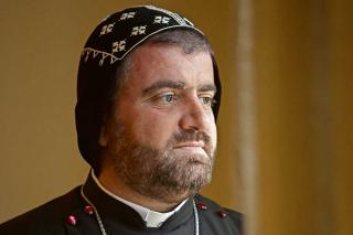 Bishop Selwanos Boutros Alnemeh stand by a window