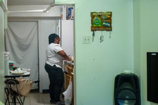 A woman stands in a kitchen preparing corn tortillas