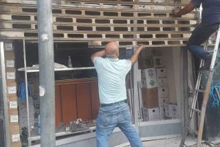 men adjusting store security gate