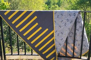 grey and gold quilt draped over railing