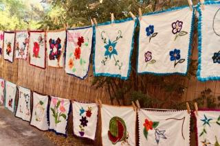 Embroidered cloths hang with clothespins on a line.