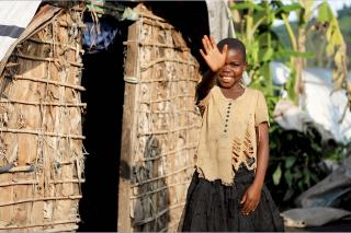 A child stands in front of a hut and waves at the camera.