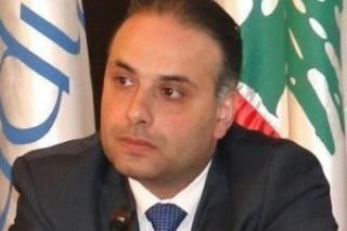A man in a suit and tie sitting in front of flags
