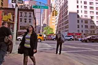 A women walks along a busy city street, a crowded intersection in the background.