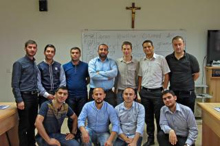 A group of men pose for a photograph in a class room with a cross on the wall.