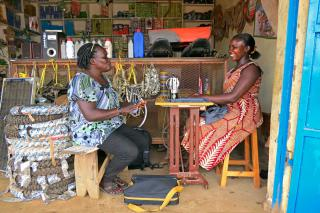 Two women talk over and sewing machine surrounded by motorcycle supplies.