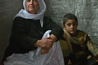 An older women and boy sit under a window in an unfinished room.