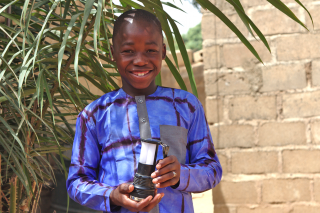 A young man holds a solar lantern.