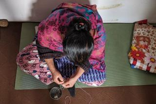 Woman sitting on a mat threading a needle.