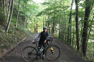 woman standing with bike on wooded trail