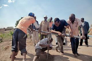 Men twist a well drilling bit into dry soil