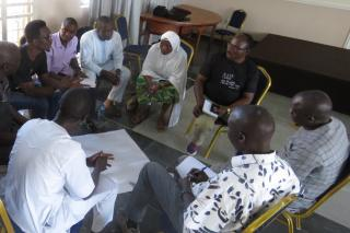 Eight men and one woman sit on chairs in a circle with one person talking and others leaning in.
