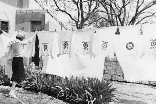 A woman hangs up Pax shirts on an outdoor clothesline.
