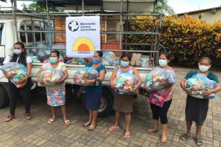 Six women stand side by side holding relief packages wearing face masks.
