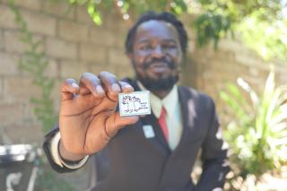 A man holds a badge with an illustration of a tree and the words Peace Club Member on it.