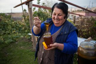 Liza spoons out honey from bees she raised through an MCC project