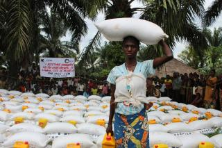 Agnès Ntumba carries a sack of corn flour and oil she received during a distribution by Communauté Evangélique Mennonite.