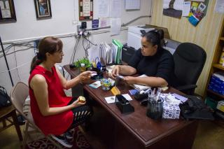 MCC staff assists client with immigration questions in office in New York City