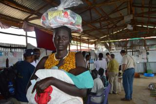 A South Sudanese refugee holding a baby carrying and relief supplies on her head