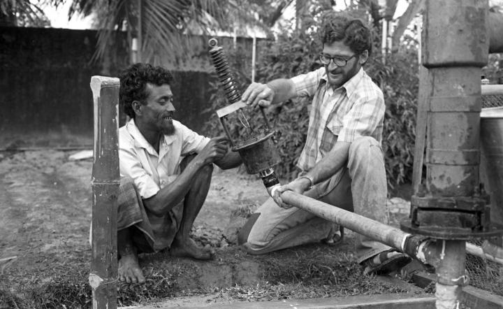 A major focus was appropriate technology, and MCC workers strove together to experiment in designing or adapting simple, inexpensive technologies that farmers could easily afford and use. In this 1979 photo in Feni, Bangladesh, MCC workers Ali Mia (left) of Feni, Bangladesh, and George Klassen of Carman, Man., experiment with a mechanical suction chamber attached to a cast-iron pump, one of many experiments that eventually led to the creation of the rower pump.