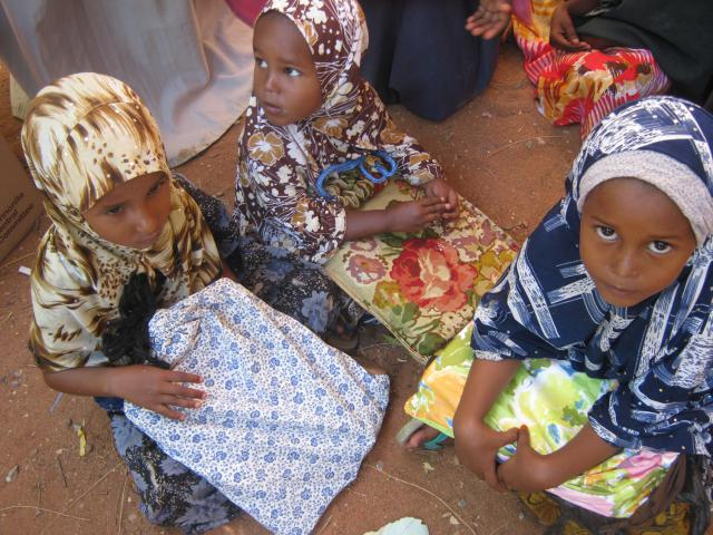 <span>At Amani Primary School in in the Dadaab refugee camp complex in northeast Kenya, sisters (from left) Fartum, Amina and Amran Abdi Kule hold their new MCC school kits. MCC responded through Lutheran World Federation to provide more than 39,000 school kits, 6,100 comforters, 500 sewing kits and some 1,300 pounds of fabric for sewing classes in the Dadaab complex.</span>