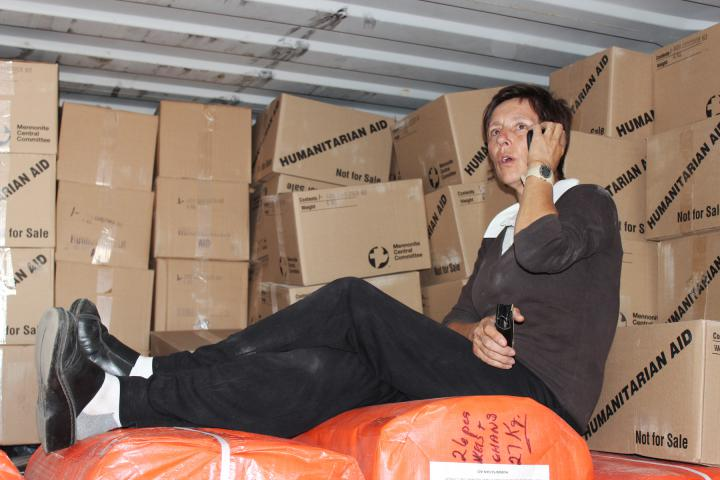 <span>In Lusaka, Zambia, Kathy Fast of Winnipeg, Man., who with her spouse Eric serves as MCC representative for Zambia, contacts MCC partners about distributing a newly arrived shipment of material resources, while taking a break from unloading items such as MCC AIDS caregiver kits, comforters, linens and mattress covers.</span>