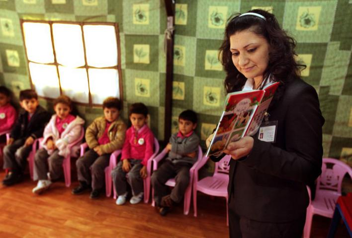 Kids House teacher Miss Ashwoq reads to her students in a classroom tent in Ankawa, a Christian suburb in Erbil, northern Iraq. Kids House is a kindergarten started in 1994 by the Chaldean Church's Sisters of the Sacred Heart of Jesus. MCC's Global Family education sponsorships help make it possible for the Sisters to accept students who cannot afford to pay tuition fees.