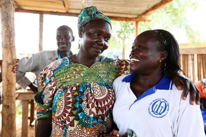 Assistant trainer Joyce Dudu (left) stands with the founder and coordinator of the tailoring project, Florence Ayikoru. In the background is tailoring trainer Mustafa Atrima.