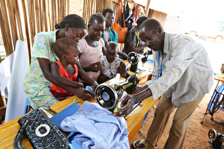 Toddlers Ester Keji (left) and Emmanuel Kenyi sit on their mother's laps while their mothers, Jerisa Muro and Hellen Poni, talk with tailoring instructor Mustafa Atrima.