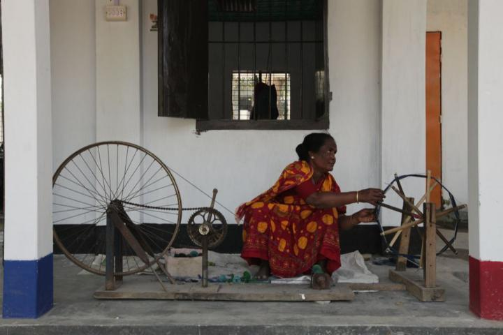 Selina Begum spins fiber created from leaves into thread. This hand machine is used to try out different combinations of fiber. Once a good combination is found it then can be produced in greater quantity.