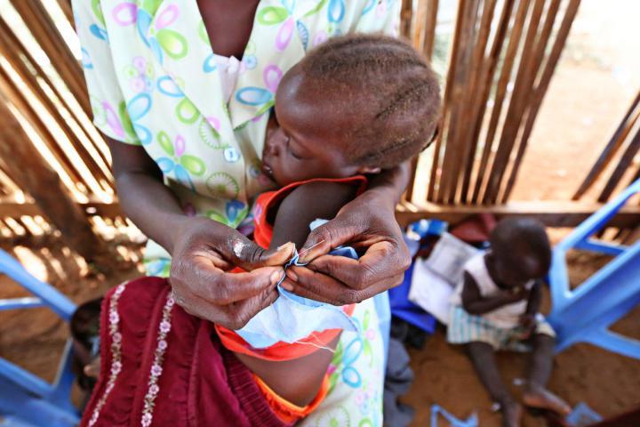 Ester Keji, 2, takes a nap while her mother Jerisa Muro sews.