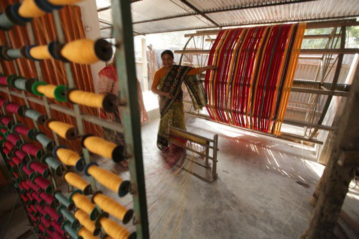 Ferdoushi Howlader shows thread that has been dyed and rolled onto spools. The threads are then used by weavers to create fabric that is later made into clothing.