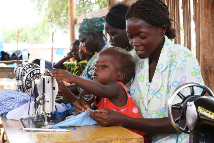 Staying close to their mothers, children become familiar with sewing machines and the sights and sounds of a sewing class. Ester Keji, 2, explores the mechanical aspects of a sewing machine while her mother Jerisa Muro is busy with her hand stitching.