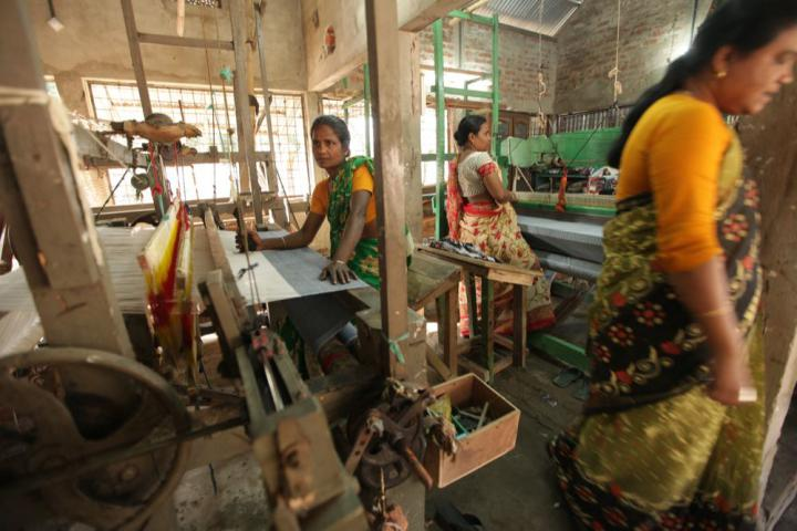 Nasima Begum, left, and Deslima Begum work at their looms to create fabric from different fibers such as cotton, pineapple and banana. Research and development with exotic fibers is important to find products that have strong appeal in local and international markets.