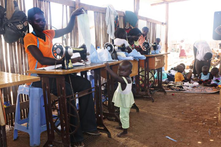 Nancy Baako sews as her daughter Winnie Alfred looks on. In the background are other children whose mothers are learning to sew.