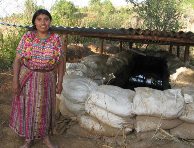 Juana Jax stands in front of a rain water catchment system that she learned about through Project Harvest. Community members helped her with the excavating and construction work that she was not able to do. The rain water will be used to water plants during the dry season, allowing Jax to grow food year round.