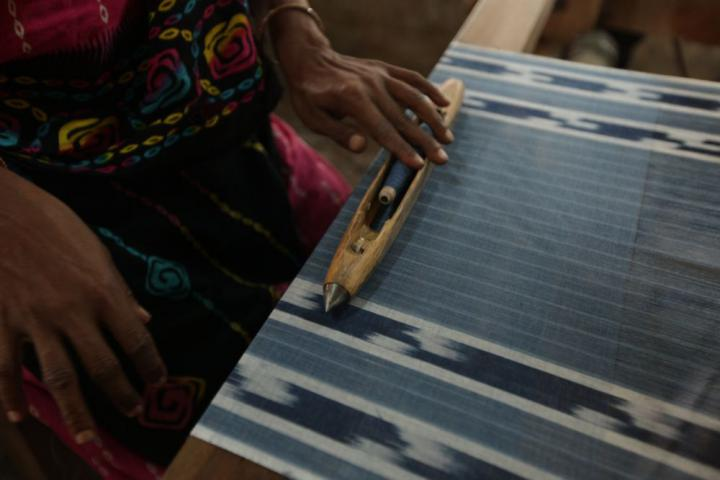 A worker adjusts a spool of indigo dyed thread as she works at her loom to create a test fabric. This type of fabric is often used for a thin shawl or head covering.