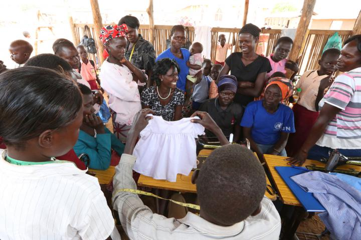 Tailoring instructor Mustafa Atrima shows the dress to students. In addition to teaching students how to sew and training them in life and business skills, leaders urge graduates to continue to come to the center for encouragement and further assistance as needed.