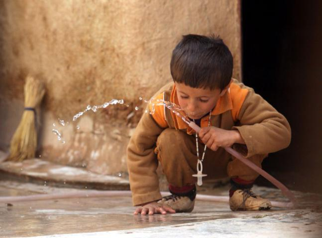 "Ramayr Khallaf, 4, drinks from a tap that brings water directly to his home in the village of Zhalay Darband. ""Water is life,"" said Dana Hassan, director of REACH. ""Water helps keep farmers on their land and increases production capacity of future years."""