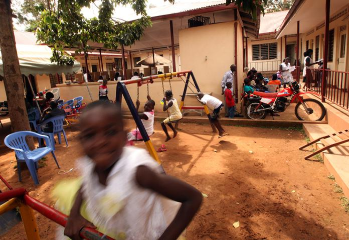 "Children use a playground at the clinic as they wait their turn to be seen by staff. For children living with HIV, the clinic provides not only treatment but a range of support, including school fees and supplies. ""I am very grateful to Mengo, because otherwise I wouldn't get any money for his education,"" says Milly Nakasujja, who is raising a 13-year-old grandson Francis Kalanzi. (Read more about this family.)"