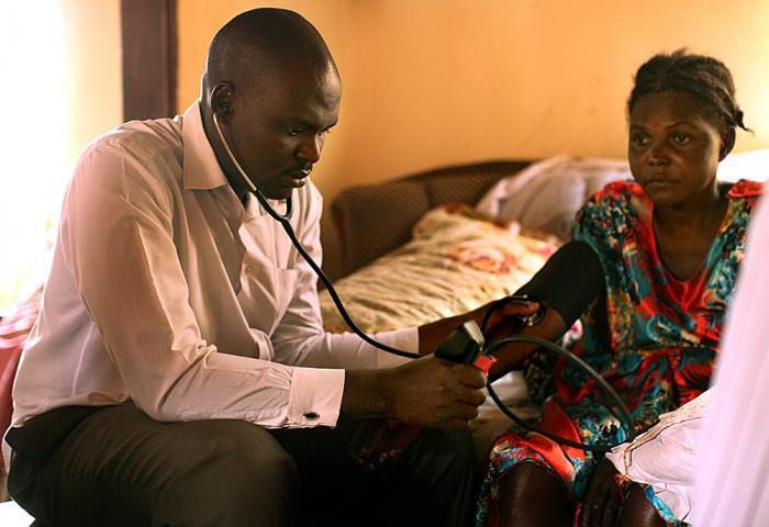 During a home care visit, Asifiwe Mumbere checks the blood pressure of 38-year-old Aisha Nabiyisha, a mother of seven who is living with HIV. In addition to HIV, she is struggling with congestive heart failure and hypertension. Mumbere is a clinical assistant, comparable to a physician's assistant.