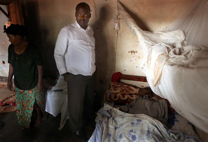 Asifiwe Mumbere monitors patient Moses Kalyango after beginning an IV. Kalyango's wife, Harriet Najjemba, is in the background.