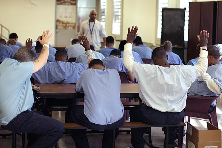 Muse encourages the inmates through prayer at the end of the Bible study.