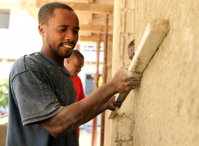 Masonry students such as 25-year-old Ronald Sadou Zami benefited from an MCC seminar on disaster-resistant construction. Zami, who has been working for a month after graduating from a masonry trade program at MCC partner FOPJ, smooths a coat of mortar at a construction site in Port-au-Prince, Haiti.