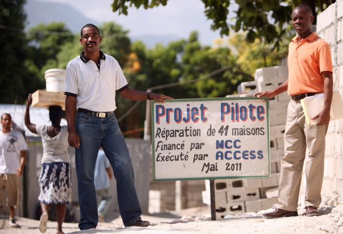 Jean Vidal, left, and Patrick Pierre, who work with MCC partner ACCESS, hold a sign for a $180,000 MCC-funded project in the Boulard neighborhood of Port-au-Prince to build five latrines and repair more than three dozen homes of recipients who were in tent camps. At least five or more people live in each of the homes that were repaired.