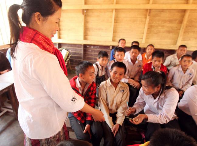 "MCC nutrition project officer Bouachan Thanvanh, shown working with students (from left) Pan, Khammoun and La, encourages pupils who help their families cook to plan meals that include several food groups. ""If you are having snails and fish meat, then add vegetables and bananas,"" she tells students. (In this area of Lao PDR, many people, including these students, use only one name.)"
