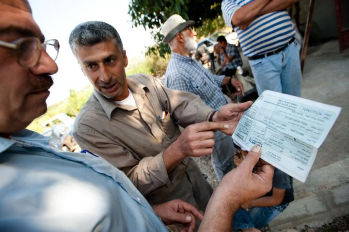 Abdul-Latif Khaled, left, a hydrologist with Palestinian Hydrology Group, and Mahmoud Muhammed Yusif, a Palestinian farmer in the West Bank, examine a permit that gives Yusif access to his land located on the other side of an Israeli separation barrier. The permit does not guarantee access to his land because the Israeli military can close the security gates at any time.