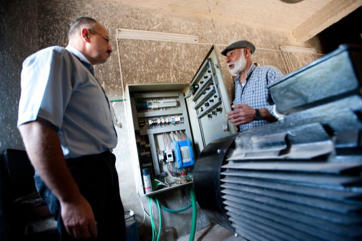 Abdul-Latif Khaled, left, a hydrologist with Palestinian Hydrology Group meets with pump manager and Palestinian farmer, Khalil Mohammed Yousef, by a rehabilitated well pump and motor. This rehabilitation project is supported by contributions to MCC's account in the Foods Resource Bank, which is owned by a number of U.S. church groups including MCC U.S.