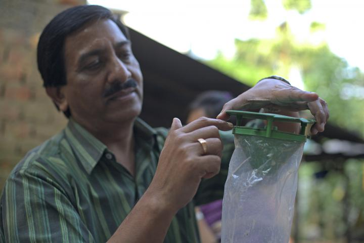 Using sustainable and organic methods to combat pests and fertilize soil gives farmers an alternative to purchasing pesticides and fertilizers each growing season. MCC project officer Achinta Das shows an insect trap supplied by ABSK.